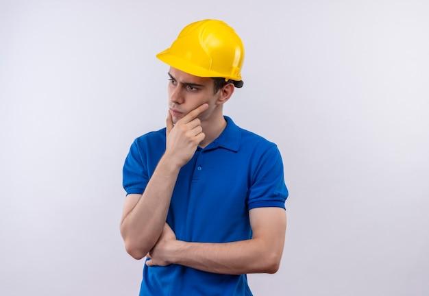 建設制服と安全ヘルメット思考を身に着けている若いビルダー男