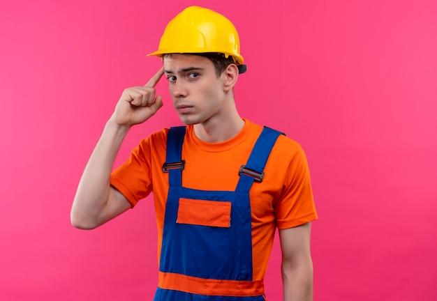 建設制服と安全ヘルメットを身に着けている若いビルダーの男は考えています