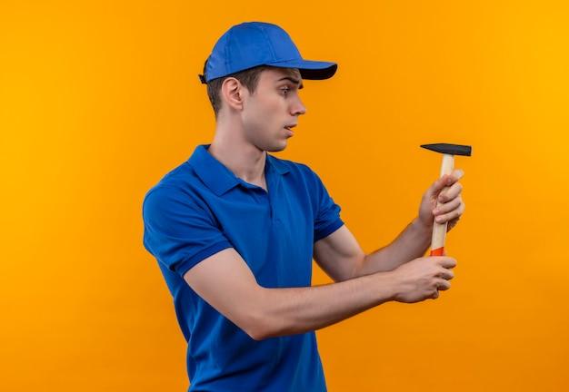 L'uomo del giovane costruttore che indossa l'uniforme e la protezione della costruzione tiene un martello premuroso