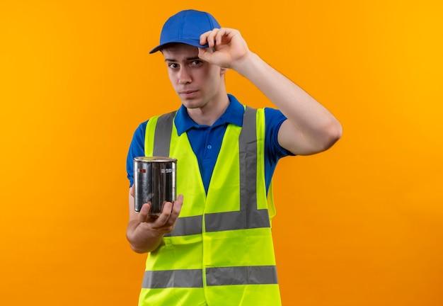 Il giovane uomo del costruttore che indossa l'uniforme e la protezione della costruzione tiene un contenitore della vernice