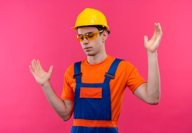Il giovane costruttore che indossa occhiali protettivi arancioni uniformi di costruzione e casco di sicurezza mostra le dimensioni