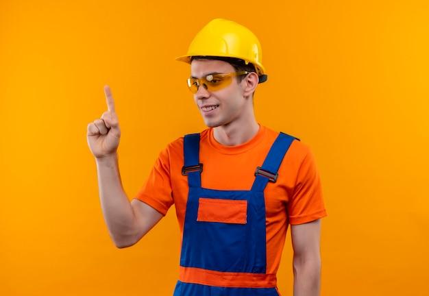 Uomo giovane costruttore indossando occhiali protettivi uniforme da costruzione e casco di sicurezza sorride e indica con i pollici