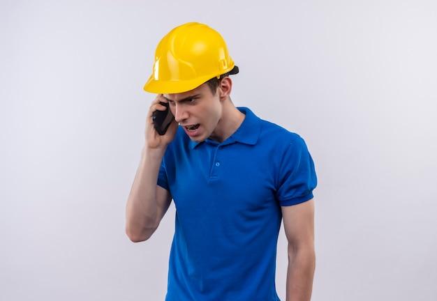L'uomo del giovane costruttore che indossa l'uniforme della costruzione e il casco di sicurezza parla con rabbia al telefono