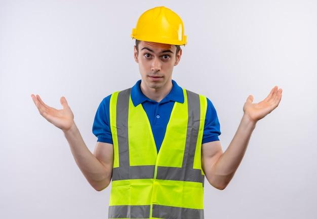 Uomo giovane costruttore indossa uniforme da costruzione e casco di sicurezza confuso