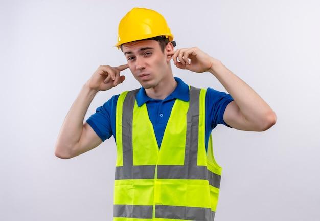 Uomo giovane costruttore indossa uniforme da costruzione e casco di sicurezza che copre le orecchie con le dita