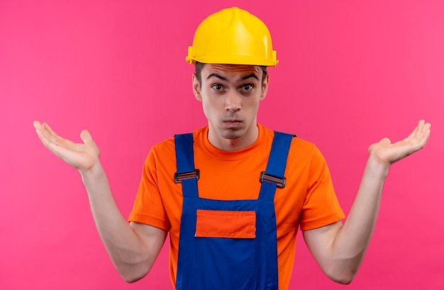 Young builder man wearing construction uniform and safety helmet doesn't know what to do