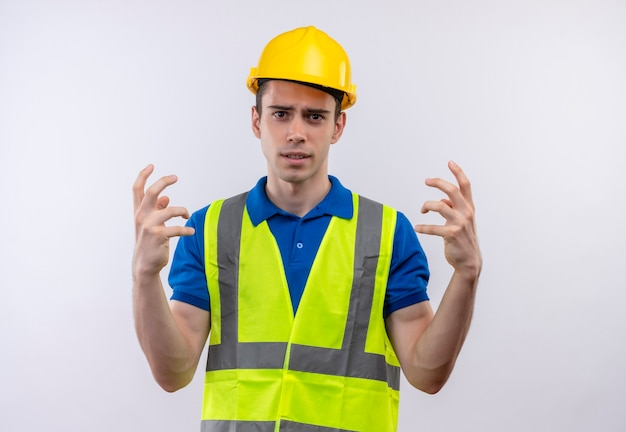 Young builder man wearing construction uniform and safety helmet fed up