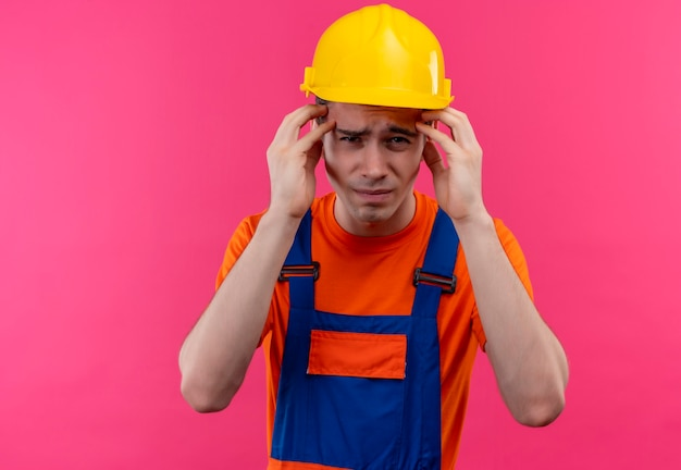Young builder man wearing construction uniform and safety helmet is fed up
