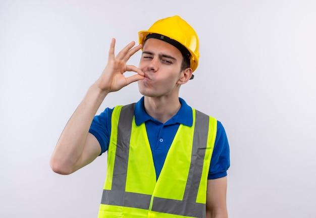 Uomo giovane costruttore che indossa l'uniforme da costruzione e il casco di sicurezza piace