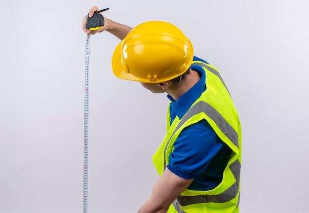 Uomo giovane costruttore indossa misure di costruzione uniforme e casco di sicurezza