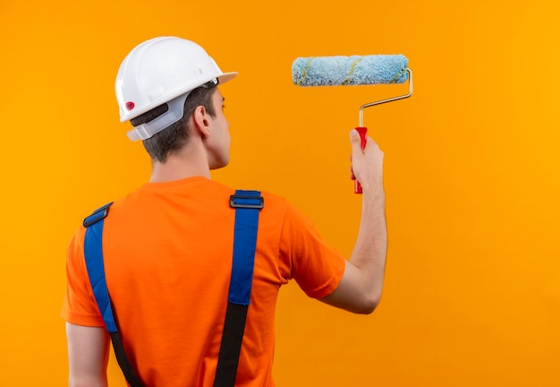 Young builder man wearing construction uniform and safety helmet paints the wall with a roller brush