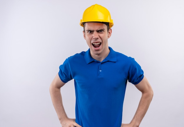 Young builder man wearing construction uniform and safety helmet shouts