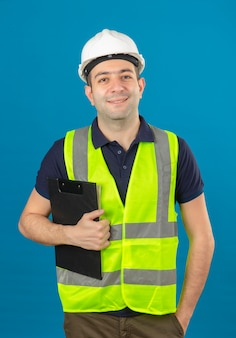 Молодой строитель мужчина носить белый шлем и желтый жилет, держа в буфер обмена с улыбкой стоя на синем изолированные