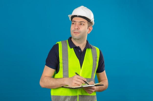 젊은 작성기 남자 흰색 헬멧과 노란색 조끼를 입고 옆으로 격리 된 클립 보드와 펜 서 들고 찾고