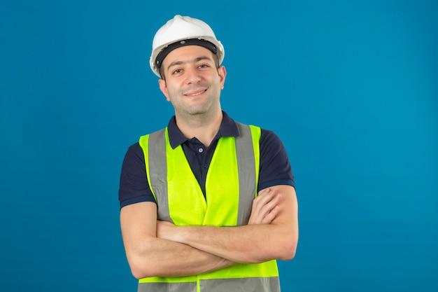 고립 된 블루에 서 웃 고 넘어 무기와 흰색 헬멧과 노란색 조끼를 입고 젊은 작성기 남자