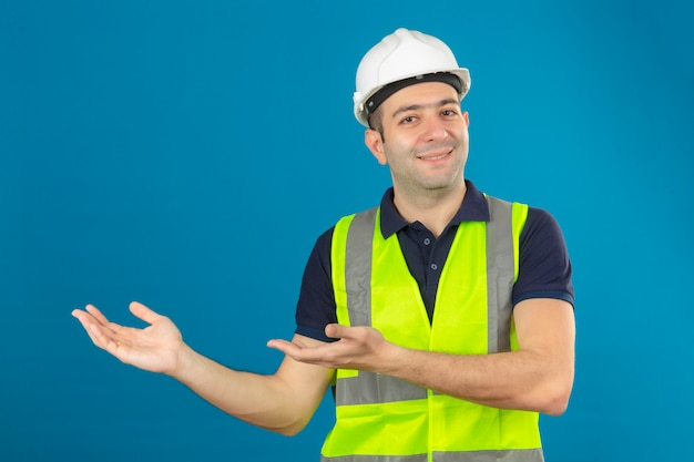 Young builder man wearing white helmet and a yellow vest, with a smile on face pointing with palm of hands at copy space on blue isolated