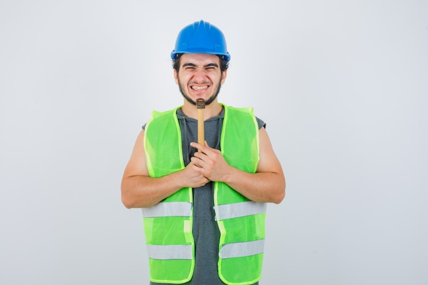 Young builder man in workwear uniform holding hammer under chin and looking merry , front view.