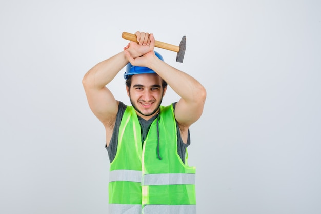 Young builder man in workwear uniform holding hammer over head and looking joyful , front view.