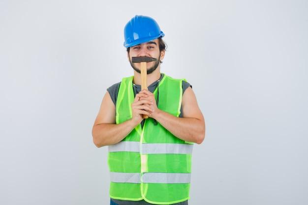Uomo giovane costruttore in uniforme da lavoro tenendo un martello sulla bocca e guardando divertente, vista frontale.