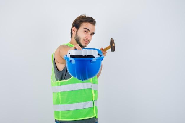 Giovane costruttore in uniforme da lavoro che tiene martello, scretching casco verso la telecamera e guardando fiducioso, vista frontale.
