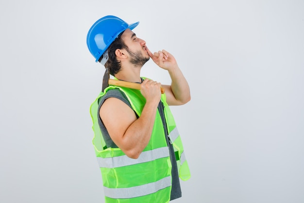 Young builder man in workwear uniform holding hammer on shoulder while showing silence gesture and looking careful , front view.