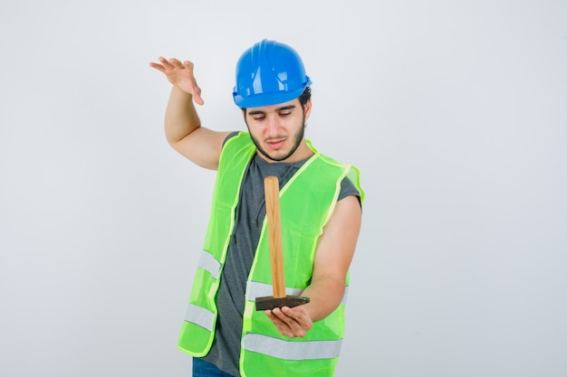 Young builder man in workwear uniform holding hammer while raising hand and looking careful , front view.