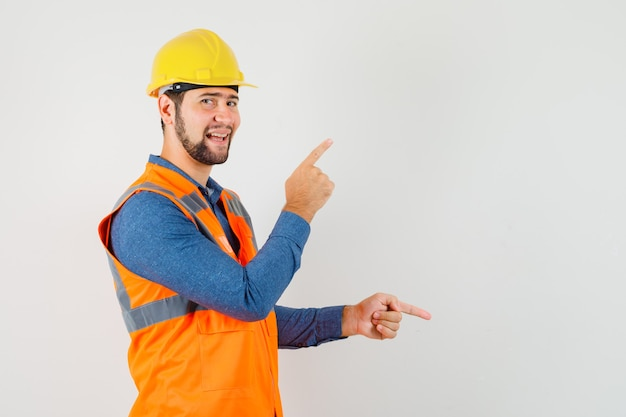 Young builder pointing fingers up and down in shirt, vest, helmet and looking cheerful. .