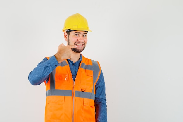 Young builder pointing at his teeth in shirt, vest, helmet and looking cheery , front view.