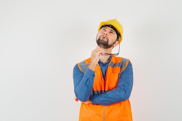 Giovane costruttore in camicia, gilet, casco mordere gli occhiali, alzando lo sguardo e guardando pensieroso, vista frontale.