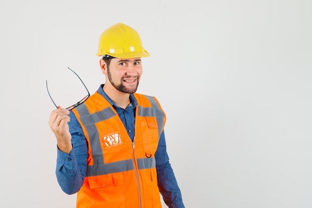 Young builder in shirt, vest, helmet holding glasses and looking cheerful , front view.