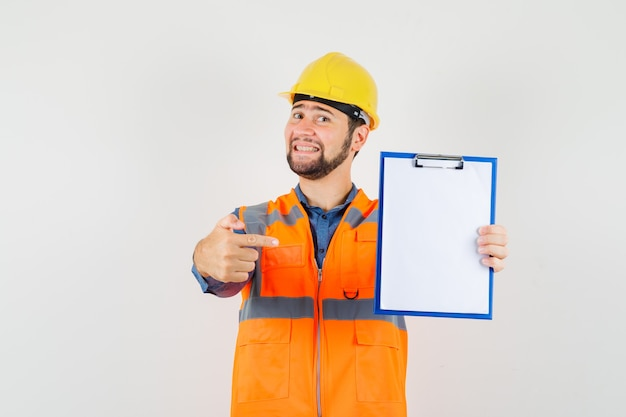 Young builder in shirt, vest, helmet pointing at clipboard and looking cheerful , front view.