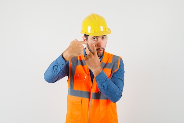 Young builder in shirt, vest, helmet pointing at his eyelid pulled by finger , front view.