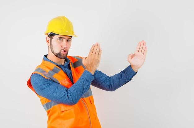 Giovane costruttore in camicia, gilet, casco che mostra il gesto di taglio di karate e sembra fiducioso, vista frontale.
