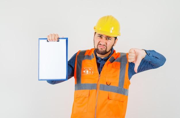 Giovane costruttore in camicia, gilet, casco che mostra il pollice verso il basso, tenendo appunti e guardando dispiaciuto, vista frontale.