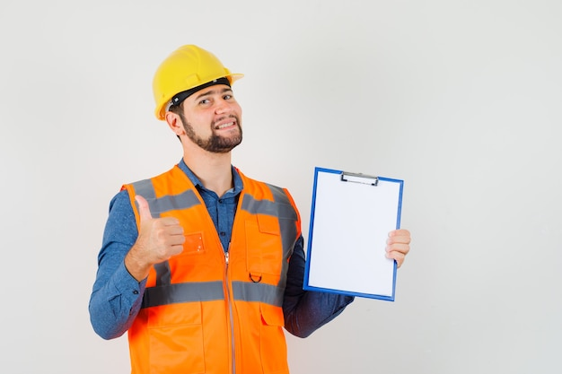 Young builder in shirt, vest, helmet showing thumb up, holding clipboard and looking glad , front view.
