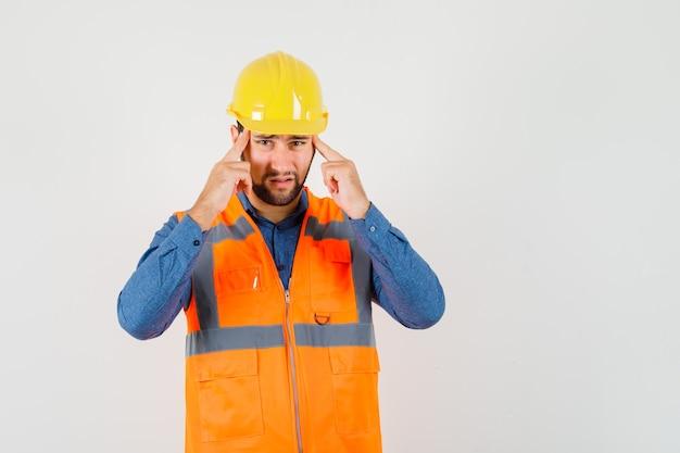 Giovane costruttore in camicia, gilet, casco soffre di forte mal di testa e sembra stanco, vista frontale.