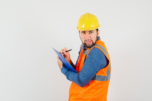 Young builder in shirt, vest, helmet taking notes on clipboard