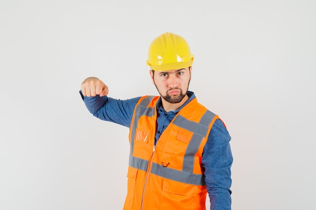 Young builder in shirt, vest, helmet threatening with fist and looking serious , front view.