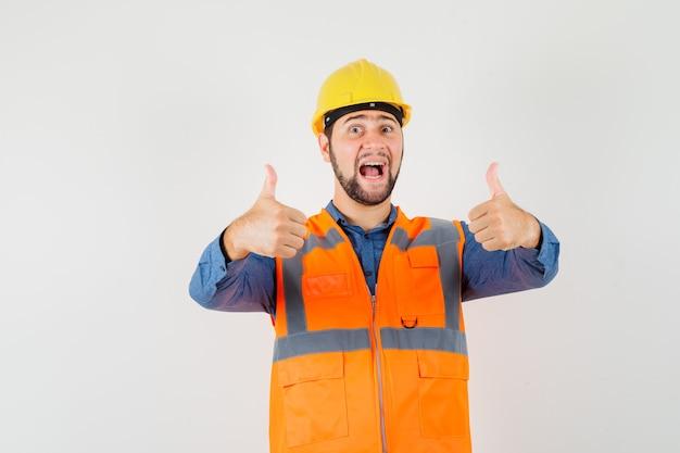 Молодой строитель показывает двойные пальцы вверх в рубашке, жилете, шлеме и выглядит удачливым, вид спереди.