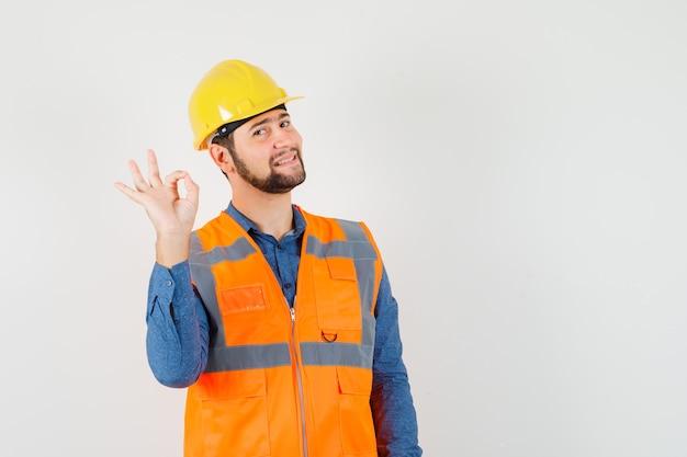 Молодой строитель показывает нормальный жест в рубашке, жилете, шлеме и выглядит веселым, вид спереди.