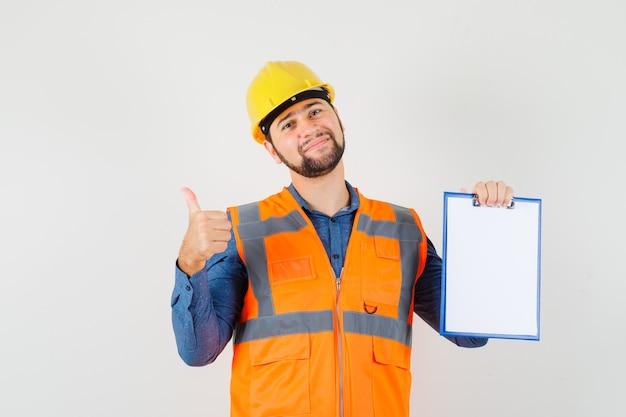 親指を立てて、シャツ、ベスト、ヘルメットにクリップボードを持ち、陽気に見える若いビルダー、正面図。