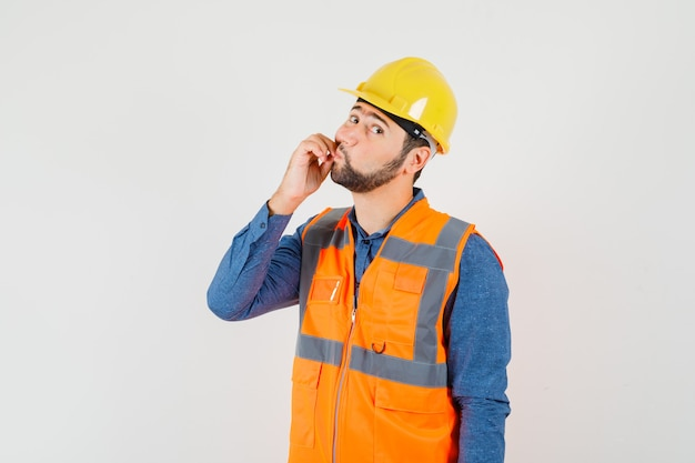 Young builder showing zip gesture in shirt, vest, helmet and looking careful , front view.