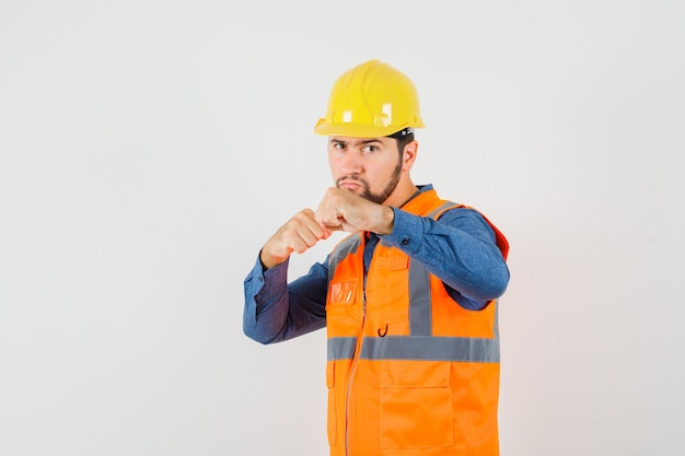 Young builder standing in boxer pose in shirt, vest, helmet and looking serious. front view.