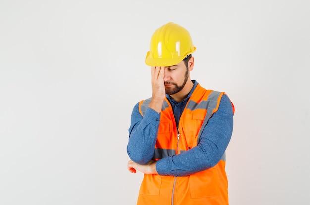 Giovane costruttore in piedi nel pensiero posa in camicia, gilet, casco e sembra stanco, vista frontale.