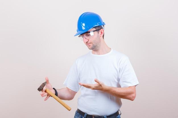 Giovane costruttore in maglietta, jeans, casco che mostra martello e sembra pensieroso