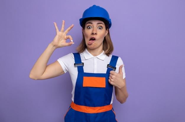 Giovane donna del costruttore in uniforme da costruzione e casco di sicurezza confuso facendo segno ok che mostra pollice in su in piedi sul viola