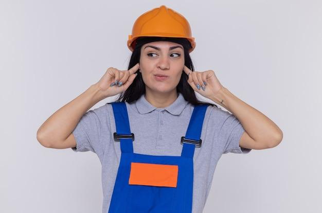 Giovane donna del costruttore in uniforme da costruzione e casco di sicurezza che copre le orecchie con le dita che sembrano confuse in piedi sopra il muro bianco