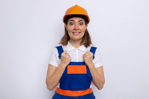 Giovane donna del costruttore in uniforme da costruzione e casco di sicurezza felice ed eccitata in piedi su un muro bianco