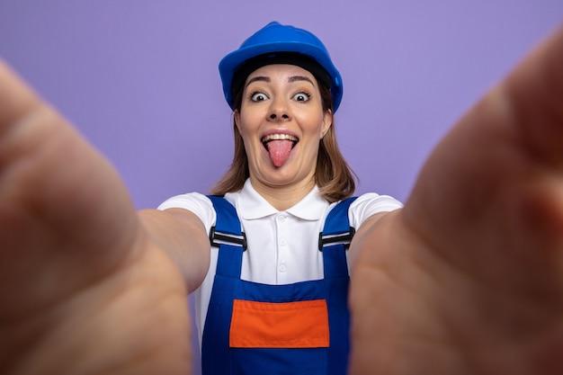 Giovane donna del costruttore in uniforme da costruzione e casco di sicurezza felice e positiva che tira fuori la lingua in piedi sul muro viola