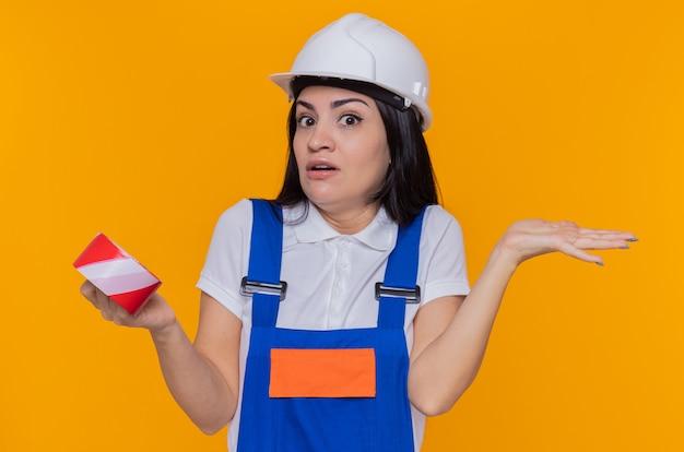 Giovane donna del costruttore in uniforme di costruzione e casco di sicurezza che tiene il nastro adesivo che guarda le spalle alzanti confuse davanti che hanno dubbi che si levano in piedi sopra la parete arancione